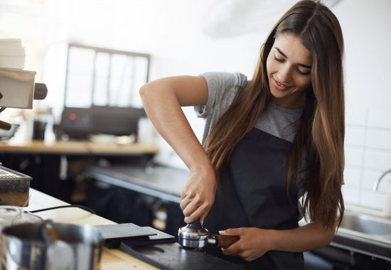 Young and beautiful female barista tamping espresso shot